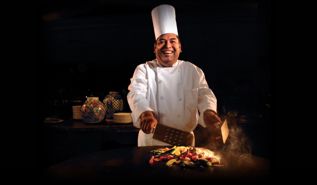 Smiling Chef preparing food on a table side flat top grill