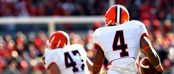Two football players in white, orange, & brown uniforms