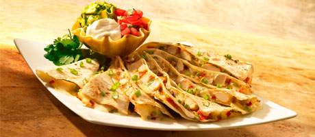 Elegant chicken quesadilla with mini tostada filled with sour cream, guacamole, and pico de gallo
