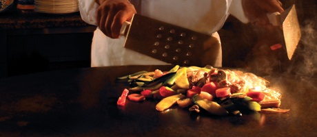 Chef with two large metal spatulas preparing stir fried vegetables on a large flat top grill