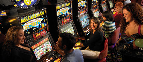 Several people enjoying slot machine play as a waitress looks on