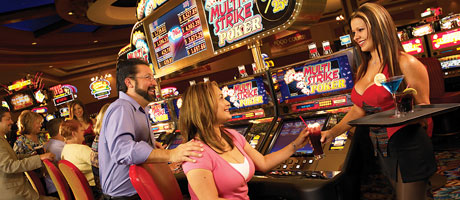 A server hands a girl a drink sitting at a slot machine